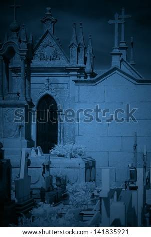 Dark old European cemetery toned blue - stock photo