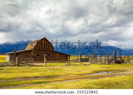 Dark, ominous clouds gather over the Teton Mountains and Moulton Barn on Mormon Row in Grand Teton National Park, Wyoming. - stock photo