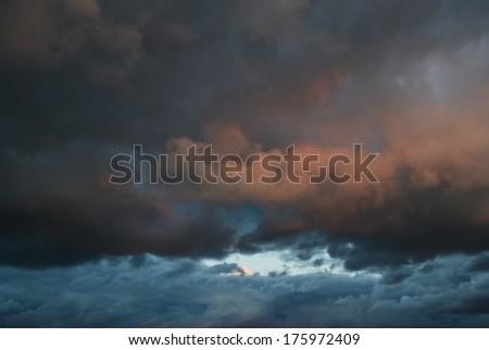 Dark ominous grey storm clouds at evening. - stock photo