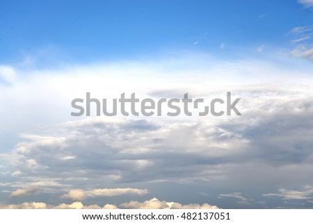 Dark, ominous rain clouds and blue sky, may be used as background.