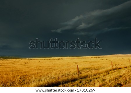 Dark, ominous storm clouds roll over golden prairie grass highlighted by the setting sun. - stock photo