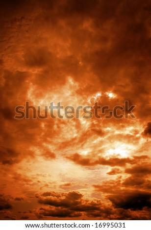 Dark orange cloudy sky at sunrise - stock photo