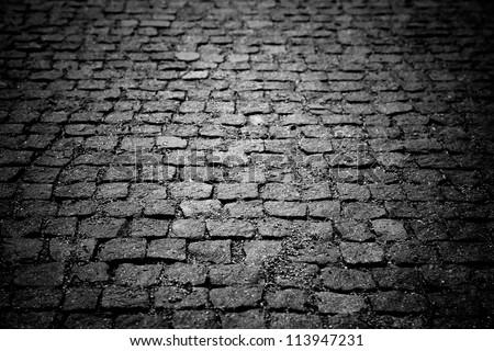 Dark paving stone roadway - stock photo