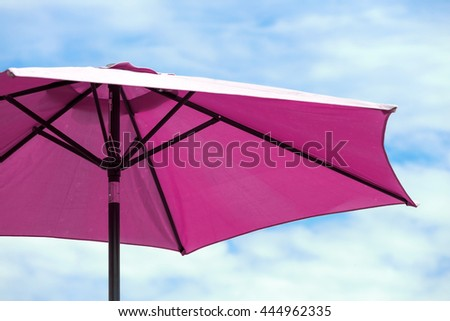 Dark pink parasol on blue cloudy sky - stock photo