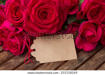 dark pink roses with empty note   on wooden  table - stock photo