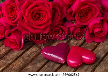 dark pink roses with two hearts  on wooden  table - stock photo