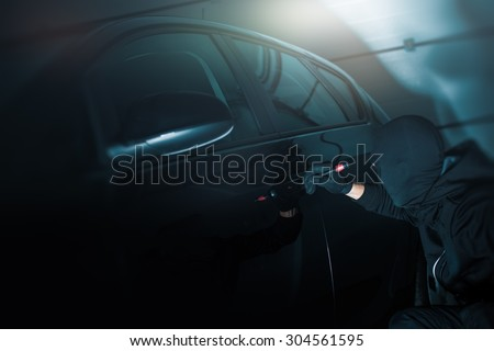 Dark Place Car Robbery. Car Robber Working to Open Cars Door.  - stock photo