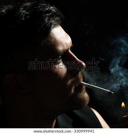 Dark portrait closeup of one young handsome sensual unshaven bearded man model half face lights up cigarette stares ahead in studio play of light and shadow on black background, square picture - stock photo