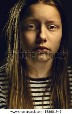 Dark portrait of a depressed teen girl, studio shot - stock photo