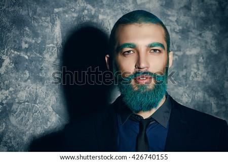 Dark portrait of a handsome man with blue beard. Folktale. - stock photo