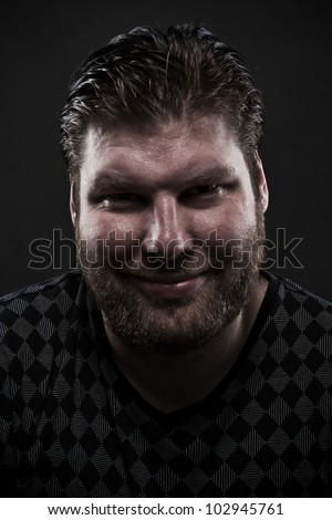 Dark portrait of a pensive smiling man - stock photo