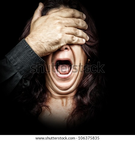 Dark portrait of a woman being abused and silenced by a man who is covering her eyes with his hand while she screams - stock photo