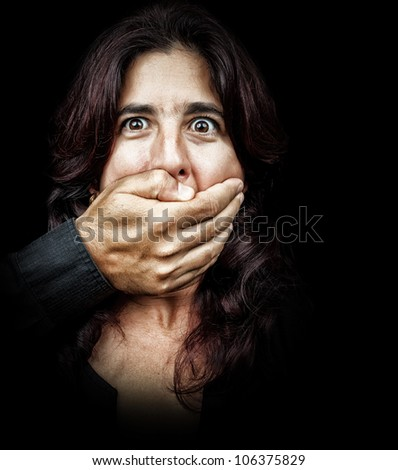 Dark portrait of a woman being abused and silenced by a man who is covering her mouth with his hand - stock photo