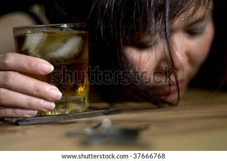 dark portrait of a woman holding an alcoholic drink - stock photo