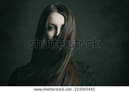 Dark portrait of a young woman with long hair . Halloween and horror concept - stock photo
