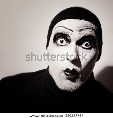 Dark portrait of actor with mime makeup on her face - stock photo