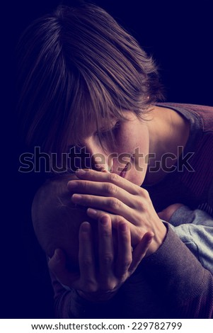 Dark portrait of an attractive loving young mother tenderly holding her newborn baby in her hands while touching his forehead with her cheek with downcast eyes and a gentle smile. - stock photo
