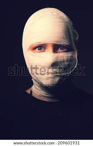 Dark portrait of an infected sick girl with a bandage on her head - stock photo