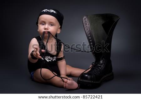 dark portrait of  rocker-baby on a black background - stock photo