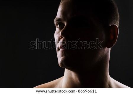 Dark portrait of strong athletic man - stock photo