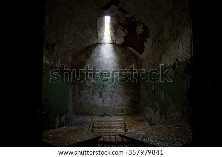 Dark prison cell with collapsing dirty walls in the Eastern State Penitentiary abandoned ruins decay - stock photo