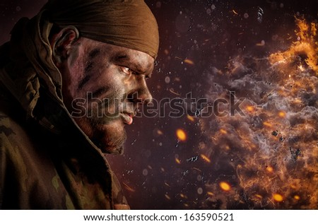 Dark profile portrait of the head and shoulders of a young man in camouflage paint and a trench coat with the collar turned up and a wearing bandanna standing in darkness with copyspace - stock photo