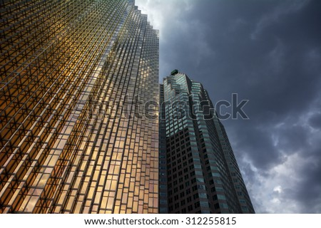 Dark rain clouds over the buildings of the financial district - stock photo