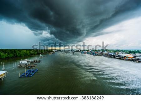 dark raincloud over a fish farm and fishing village - stock photo