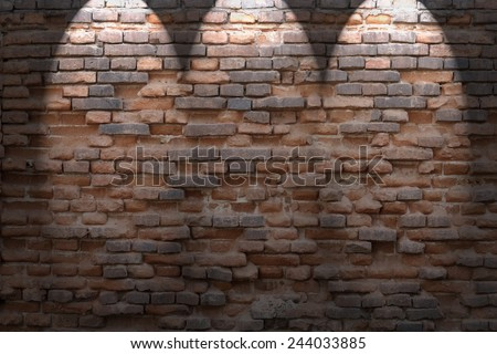 dark red brick wall background in basement with beams of spot lights - stock photo