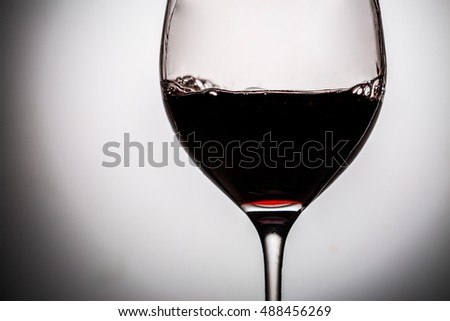 Dark red wine in glass filled it half. Image on a light gray background