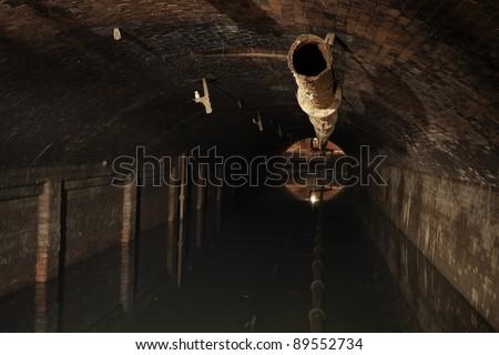 Dark reservoir of sludge - underground historical sewage treatment plant in Prague. - stock photo