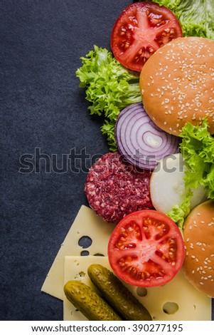 Dark restaurant menu, burger ingredients and copy space. Dark slate from above. - stock photo