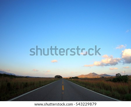 Dark road leading to a bright horizon