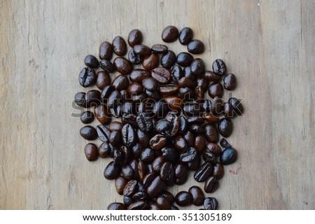dark roast coffee bean on wooden board - stock photo