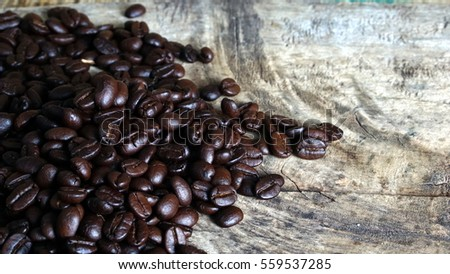 Dark roasted coffee beans on a the old wood