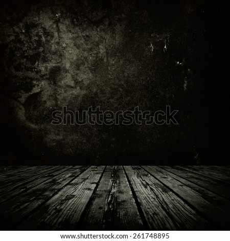 Dark room with stone or masonry wall and grungy old  wooden floor. - stock photo