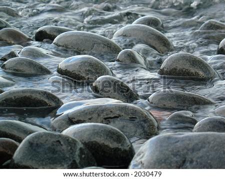dark round rocks on the Lake Superior shoreline - stock photo