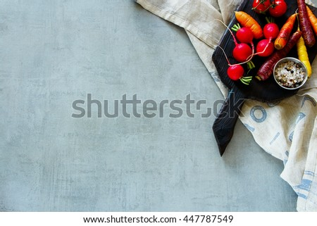 Dark rustic cutting board with raw organic vegetables over grey background. Healthy food. Vegetarian eating. Fresh harvest from the garden. Flat lay. Copy space for text. - stock photo