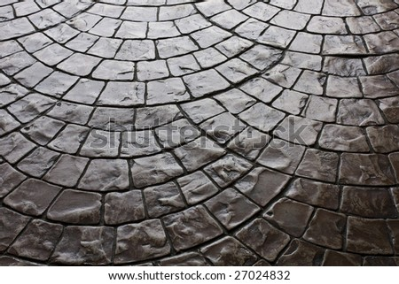 Dark rustic floor paving stones laid in a rounded pattern - stock photo