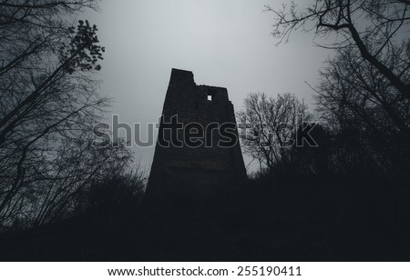 dark scene castle tower and spooky twisted tree branches at night - stock photo