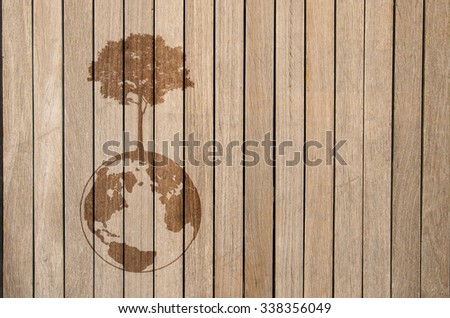 dark shadow of growing tree plant on earth sphere map graphic, on light brown wooden background. ecology concept - stock photo
