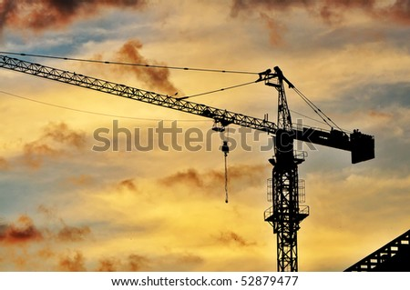 Dark silhouette of a construction crane at dusk, against warm orange sky. - stock photo