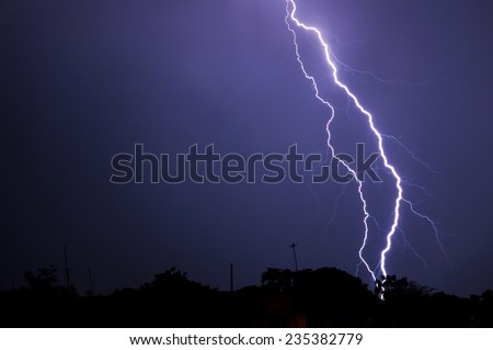 Dark silhouette of town as intense electrifying lightning bolt strikes the ground
