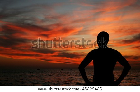 dark silhouette of young man on the beach