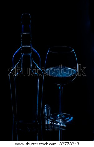 Dark silhouetted  shape of a bottles with glass of wine
