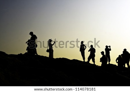 Dark silhouettes of tourists taking photos at sunset on a hill