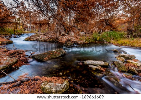 Dark Silky Flowing Waterfalls Along the Guadalupe River Surrounded by Beautiful Fall Foliage, Texas. - stock photo