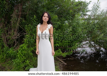 dark-skinned, dark-haired girl in a white dress near the pond. beautiful young bride on the river bank