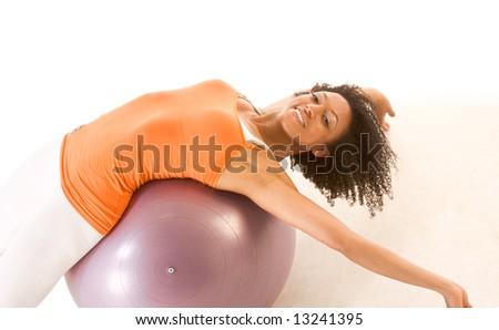 Dark skinned female stretching on exercise ball - stock photo