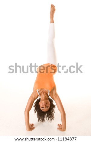 Dark skinned female stretching with one leg up in the air - stock photo